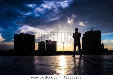 Male office worker Stand on the deck There is light Make a silhouette.