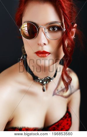 beautiful steampunk girl with bodypainting on her shoulder posing at studio in black corsette and red skirt