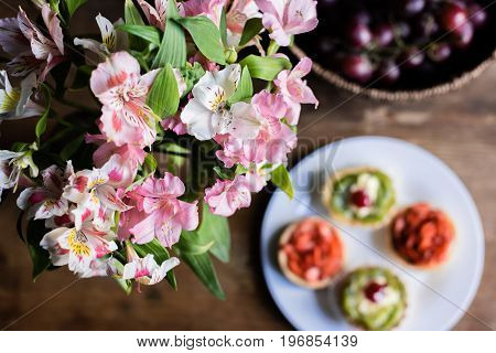 Still Life Of Flowers, Breakfast With Cakes And Fruits On Kitchen Table