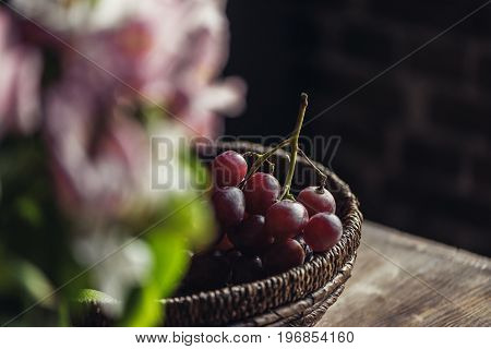 Close-up Basket Of Red Grapes On Kitchen Table And Blurred Flowers In Foreground