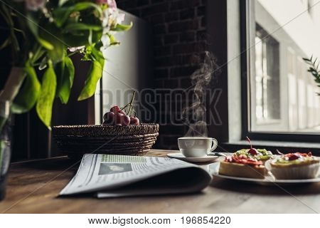 Still Life Of Newspaper, Breakfast With Cakes And Hot Coffee On Kitchen Table In Front Of Window