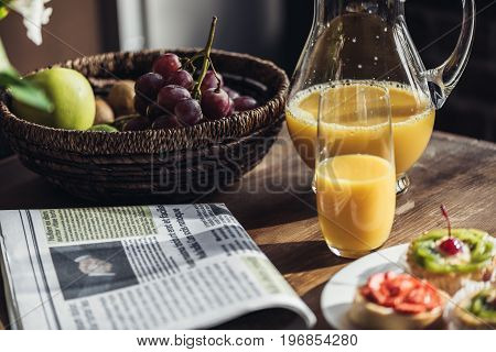 Still Life Of Newspaper, Breakfast With Cakes, Juice And  Fruits On Kitchen Table In Front Of Window
