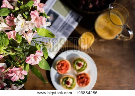 Still Life Of Flowers, Newspaper, Breakfast With Cakes And Glass Of Juice On Kitchen Table
