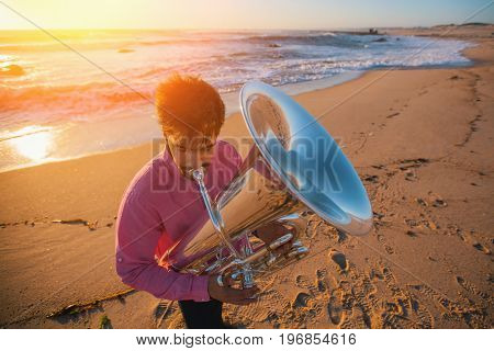 Young musician playing the trumpet on the sea coast.