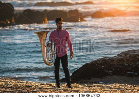 Young musician with trumpet on the sea coast during surf. Tuba instrument.