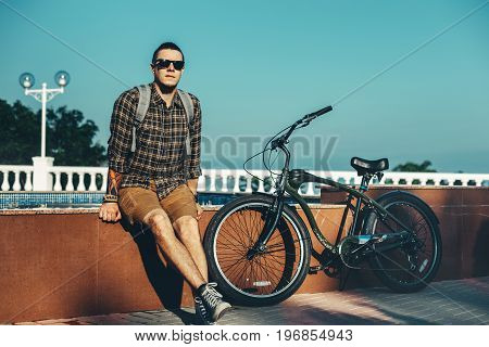 Young Man In Sunglasses Sitting On Fountain Next To Bicycle In Summer Park Daily Lifestyle Urban Resting Concept