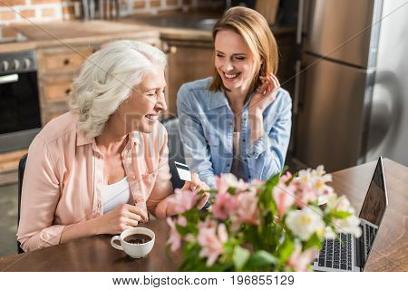 Young And Senior Women Sitting At Table And Using Laptop In Kitchen