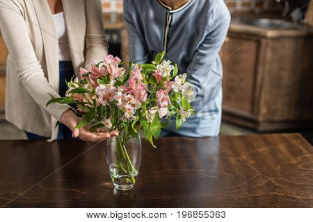 Young Pregnant Woman And Her Senior Mother With Bouquet Of Flowers On Kitchen