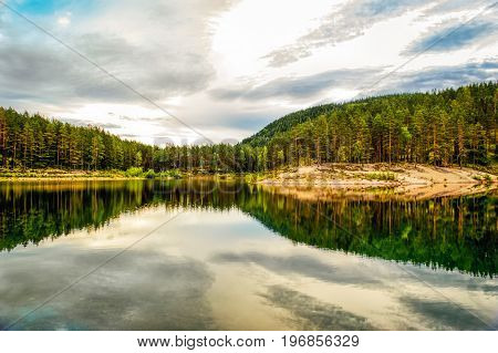 Beautiful evening sun view over the green water of Green Tarn a nature reserve in Sweden