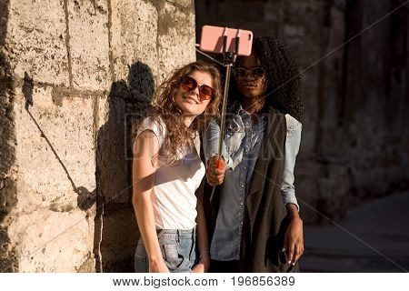 Two attractive girls wearing casual closes and glasses making selfie near the wall. One girl is african american.