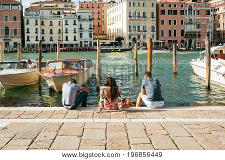 VENICE, ITALY - JULY 03, 2017: Tourists relax on the steps of Grand Canal, Venice. Venice is a popular tourist destination for its uniqueness, celebrated art and architecture.