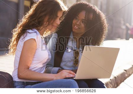 Two beautiful young women having conversation. Women sitting on the pavement wit the laptop. One woman is black.