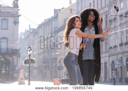 Two happy girls making selfie on thebeautiful street. Sunny day and good weather. One girl is black.