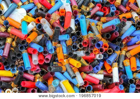 Many shotgun shells of various colors background texture pattern with empty fired cartridges.