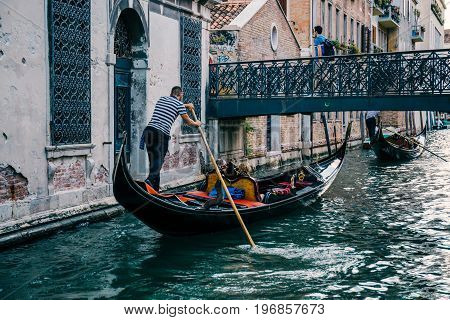 VENICE, ITALY - JULY 01, 2017: Gondola with tourists on a canal in Venice. Venice is a popular tourist destination for its uniqueness and architecture.