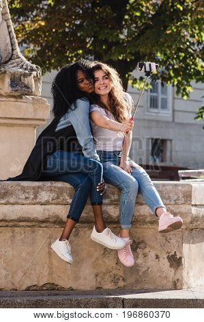 Two young abd beautiful women making selfie near the monument in the downtown. Women wearing casual clothes. One woman is black.