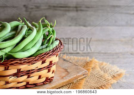 Green string beans in a wicker basket and a burlap. Natural unripe beans pods. Rustic wooden background with copy space for text. Green string beans harvest concept