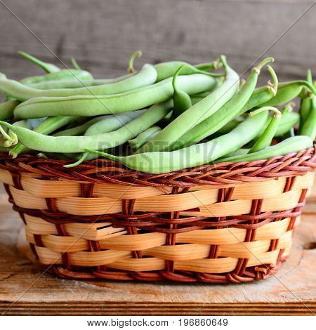 Green string beans in a wicker basket and a wooden board. Raw young beans pods. Old wooden background. Seasonal harvest concept. Closeup