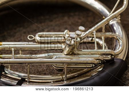 a sousaphone resting on the floor waiting for its turn to perform