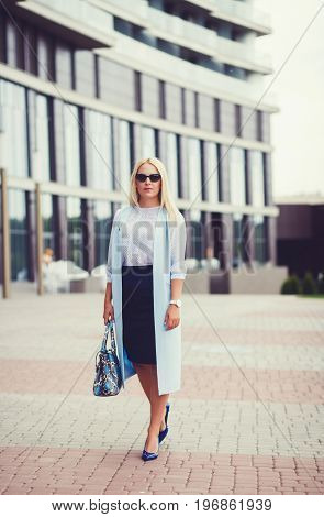 Business lady in a blue coat near an office building with a bag