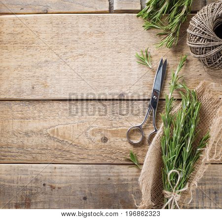 Aromatic twigs of rosemary scissors and cord on the wood