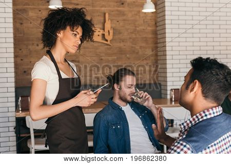 Young African American Woman Waitress Taking Orders From Clients In Cafe