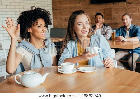 Two Young Women Having Tea In Cafe And Men Sitting At Next Table Looking At Them