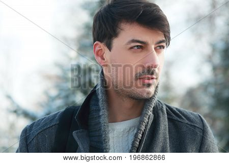 trendy stylish young man wearing coat in winter par