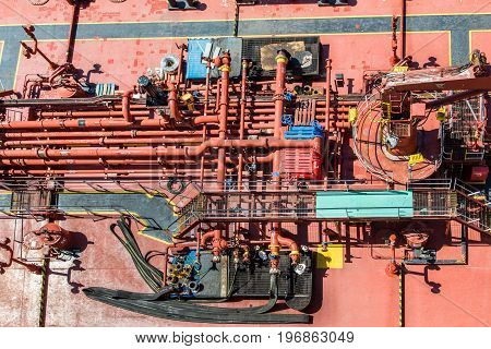Deck of a Huge Red Tanker with many pipes and valves