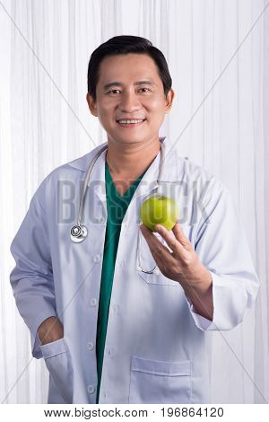 Nurse or male doctor giving an apple smiling. Health care concept isolated on white background.
