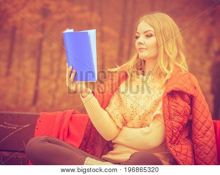 Nature outdoor relax leisure literature concept. Lady reading blue book. Young blonde girl in autumnal forest sitting on bench covered by blanket.