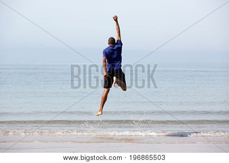 Young Black Guy Jumping By The Beach