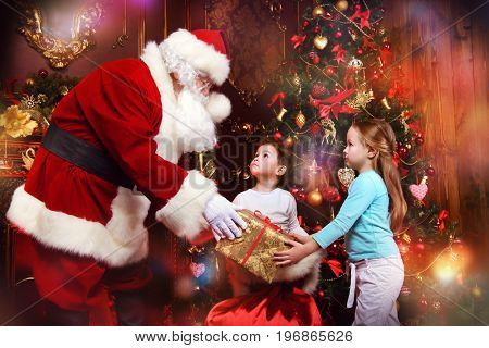Cute funny children ask Santa Claus about gifts. Beautiful room with Christmas tree and fireplace decorated for Christmas.