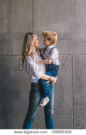 Mother and son hugging on the wall background