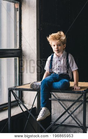 Little boy sitting on a table near a window
