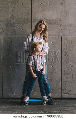 Mother with son on the skateboard standing at a wall