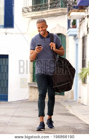 Smiling Young Black Guy Traveling With Bag And Using Mobile Phone On The Street