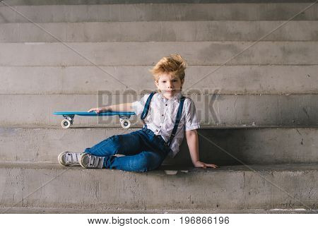 Little boy sitting with a skateboard on the stairs