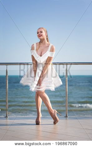 A fashionable, gorgeous lady on a transparent terrace on a bright blue sky background. A stylish girl with a long dark blonde ponytail. A joyful young woman in a white dress outside.