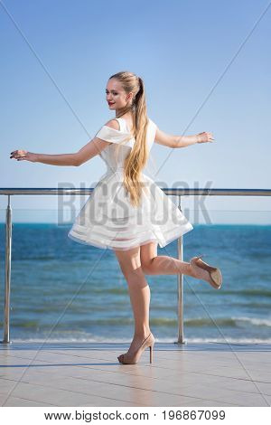 A fashionable gorgeous lady on a transparent terrace on a bright blue sky background. A stylish girl with a long dark blonde ponytail. A joyful young woman in a white dress outside.