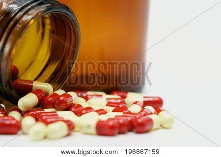 Antibiotic capsule pills with amber glass bottle on white background