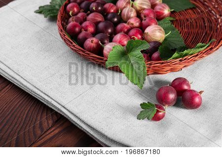 Juicy, tasty different shades of bright red color gooseberries with leaves in a wooden basket. A brown basket on a gray fabric and on a wooden table. Nutritious fruit ingredient. Colorful red berries.