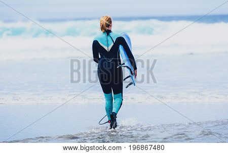 Surfer woman with surfboard is walking and watching the waves. Girl in surfing wet suit is observing the waves of cold atlantic ocean in Galicia Spain.