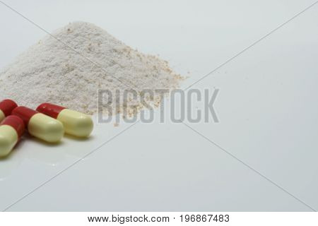 Antibiotic capsules and dry powder medicine on white background