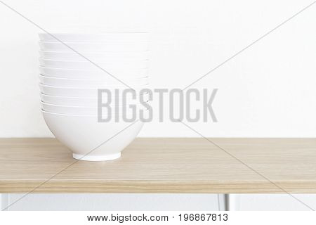 Stack of white bowls on wooden table and white background. (with Clipping Path)