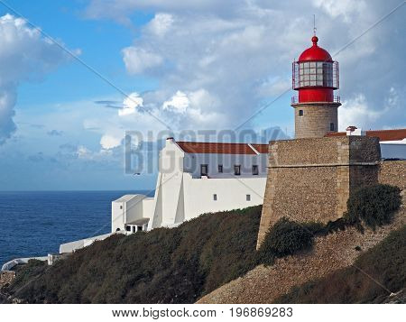 red lighthouse on Cabo de Sao Vicente with stone wall and white house