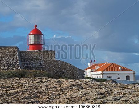 red lighthouse on Cabo de Sao Vicente with stone wall and house and blue sky