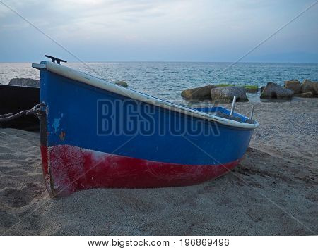 red blue fishing boat on the sand on the beach with moss rock