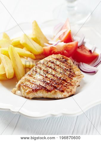 Grilled turkey breast fillet with tomatoes and french fries