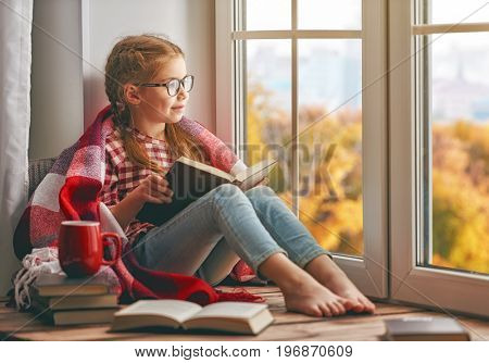 Cute child girl sitting by the window and reading a book in room at home. Beautiful autumn nature.